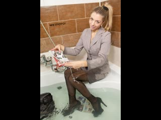 Full wet business lady in classic suit, tights and high heels meeting in bath