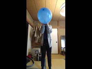 Asian woman blow to pop blue balloon
