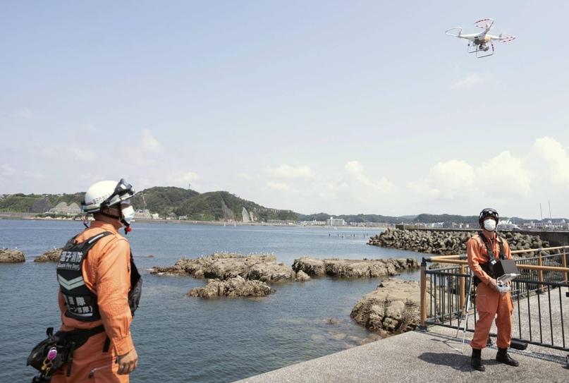 В рамках спасательных учений пожарные летают на беспилотнике над водами Хаямы, префектура Канагава.